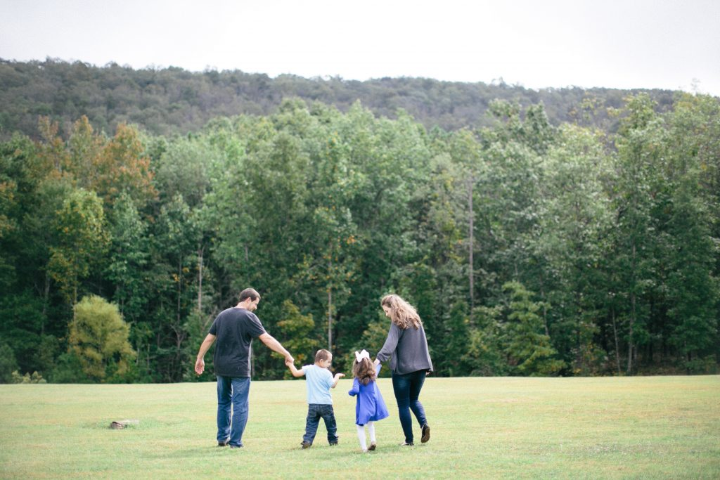 parish family of 4 walking through a field holding hands